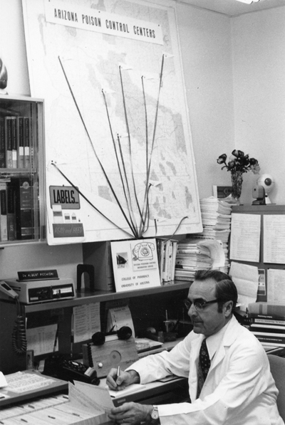 1950 era photo of man at desk with map behind